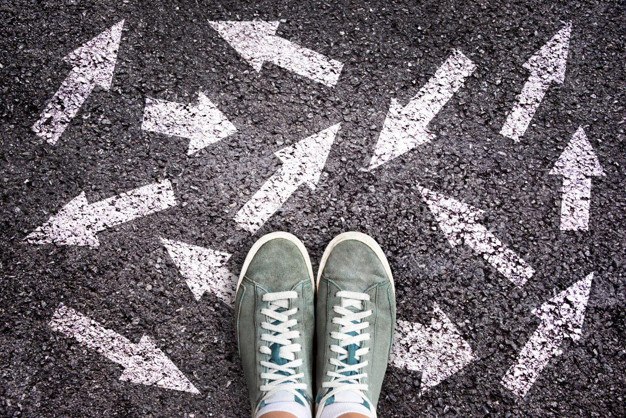 Et par sko som står på asfalt med piler i ulike retninger