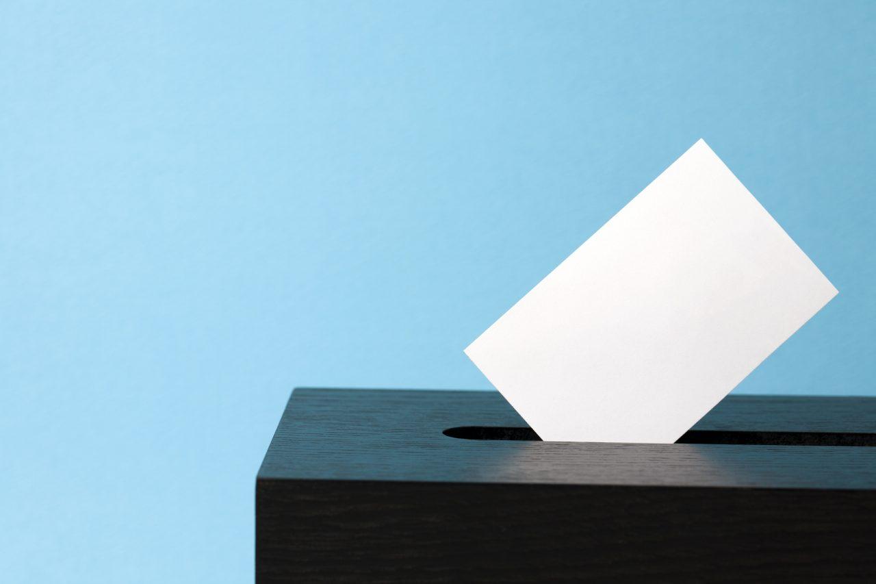 Stemmeseddel blir lagt i urne