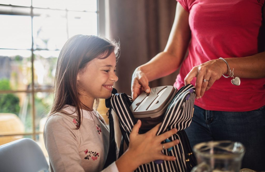 Smilende ung jente med stripete skolesekk. Mor i bagrunnen som legger matboks i sekken.