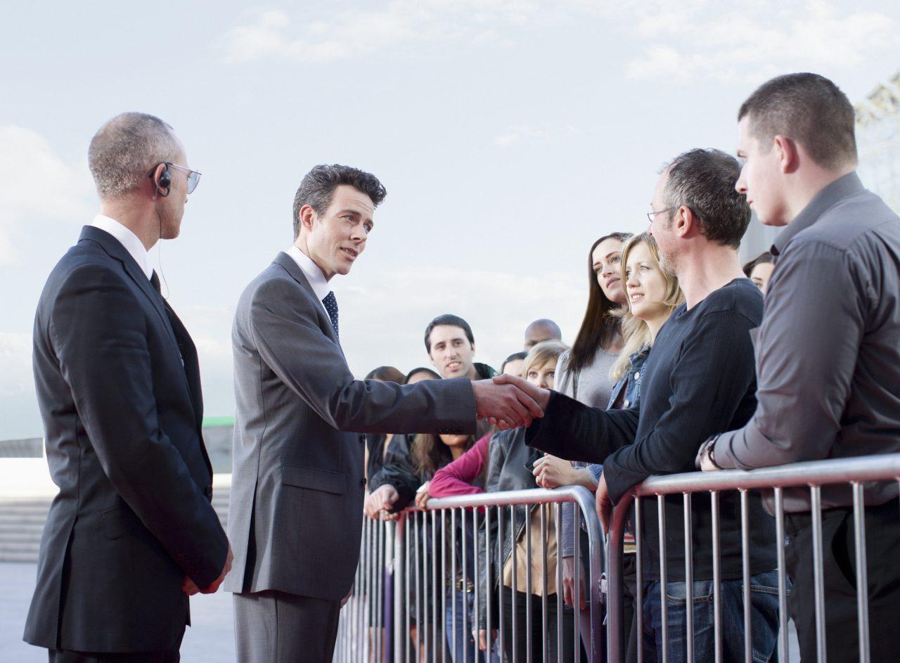 Politiker som står og snakker med en menneske mengde med en livvakt ved siden av seg