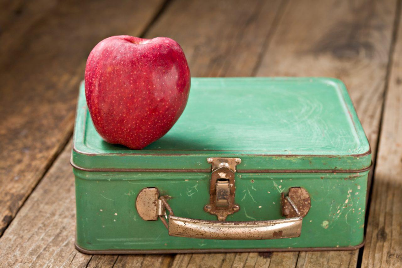 Retro grønn matbokskoffert i metall mot en rustikk treoverflate. Knallrødt eple oppå matboksen.