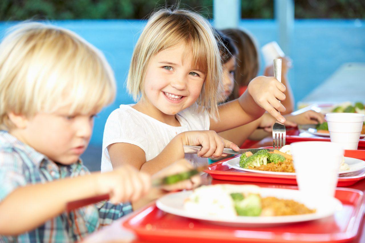 Fornøyde skolebarn i kantine spiser varmmat.