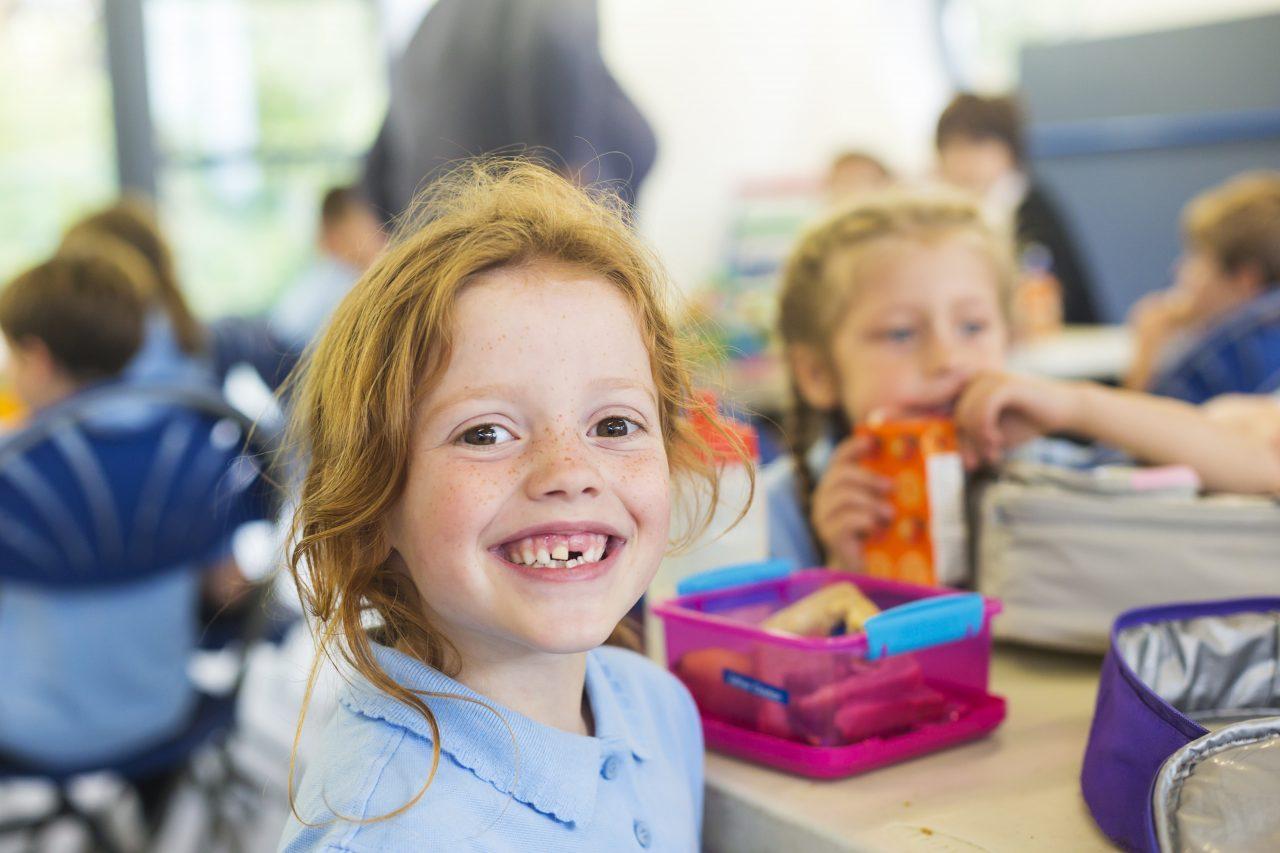 Jente med klasserom i bakrunnen. Vi kan skiimte en rosa matpakke på pulten hennes, og en klassekamerat som er i ferd med så spise sin lunsj.
