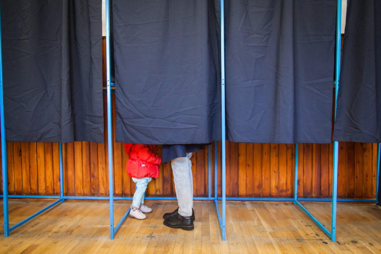 Et stemmelokale med et avlukke med gardin. Vi ser føttene til en voksen og et barn inni avlukket.