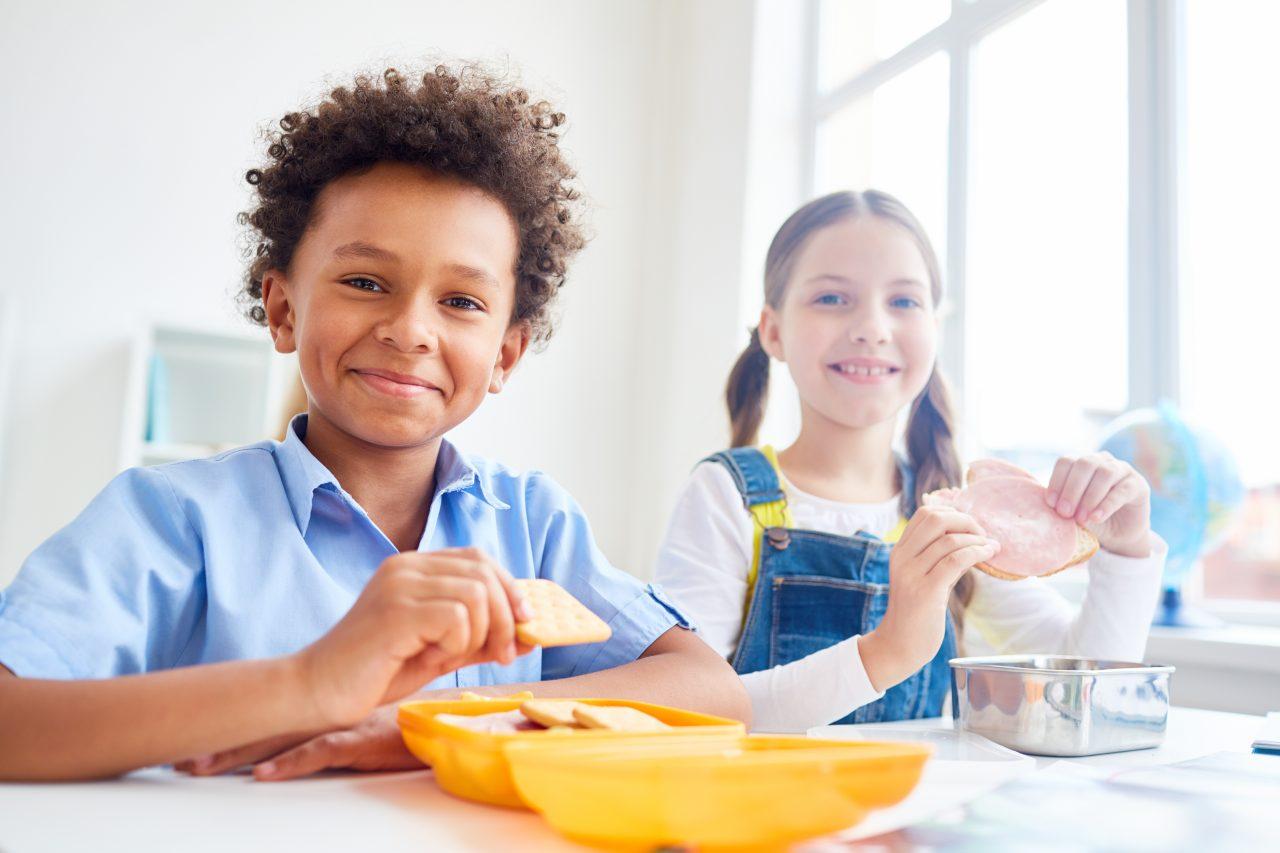 Ung gutt og jente i klasserom. Gutten spiser kjeks fra en gul matboks, og jenten holder en skive.
