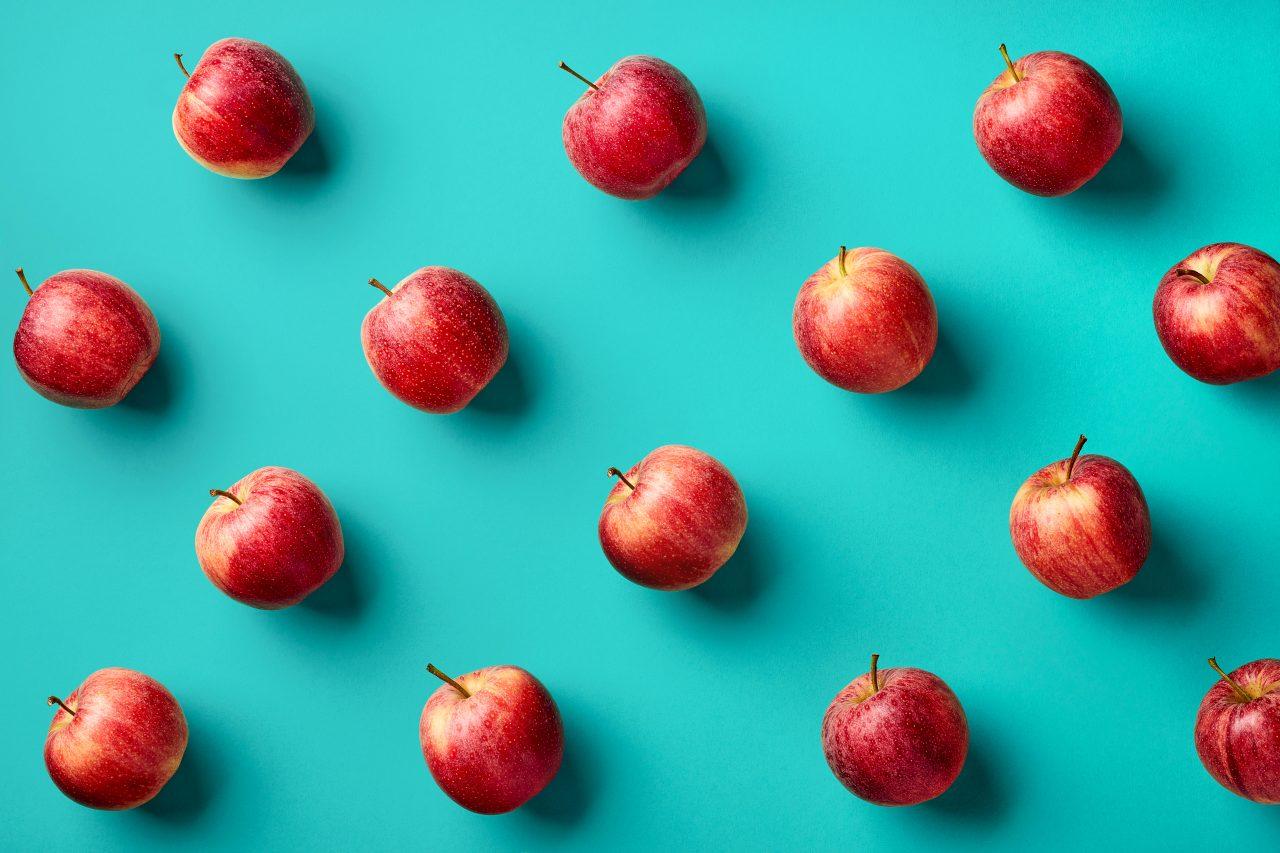 Røde epler dandert i et mønster mot en knallturkis bakgrunn.
