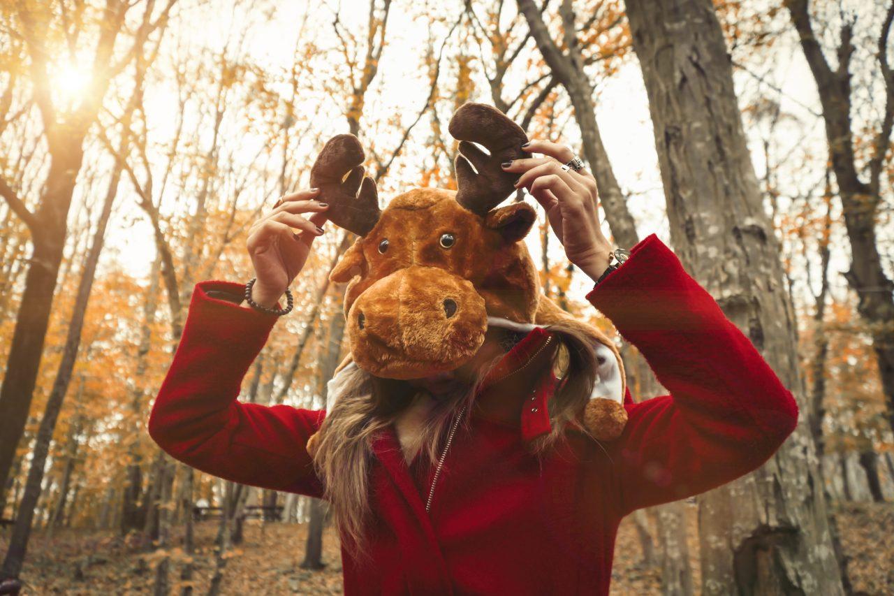 Kvinne i skogen, med elgmaske holder på geviet i stoff.