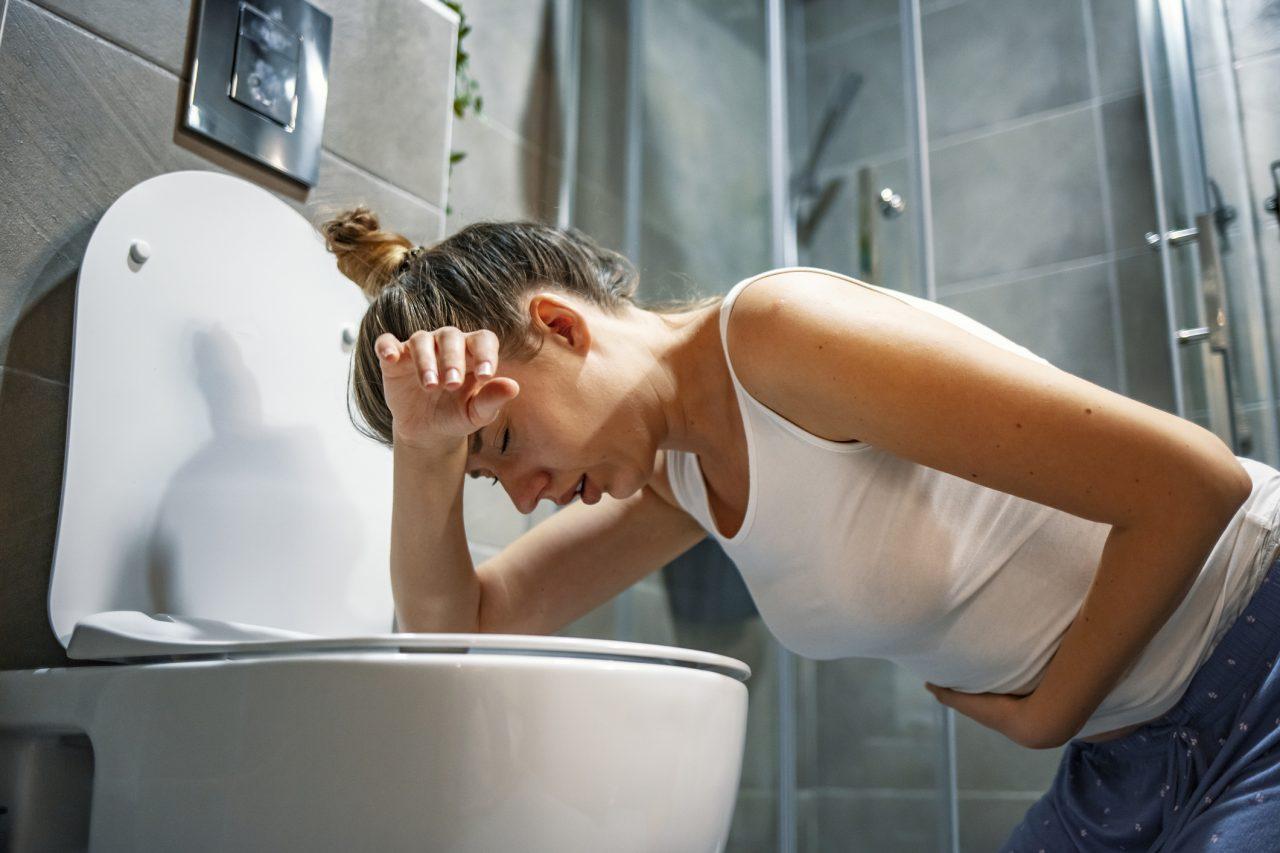 Ung kvinne som er syk og sitter på baderomsgulvet lent over toalettskåla