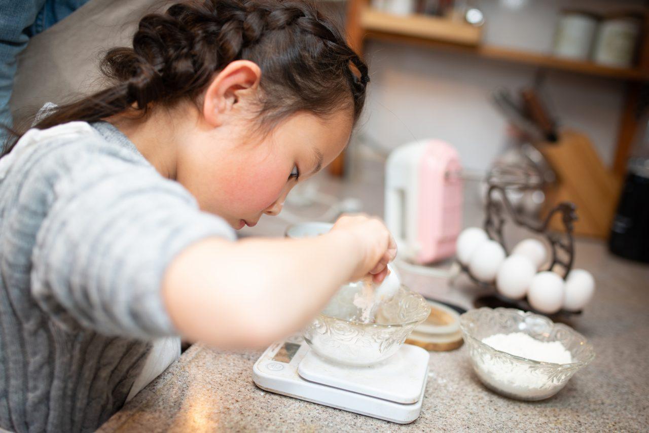 Jente som veier opp mel til baking