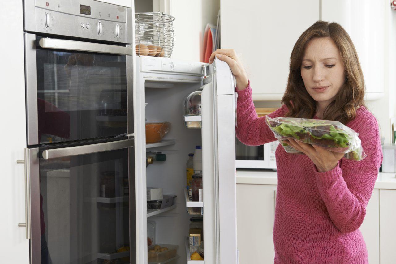 Kvinne sjekker utløpsdato på en pakke med salat fra kjøleskapet