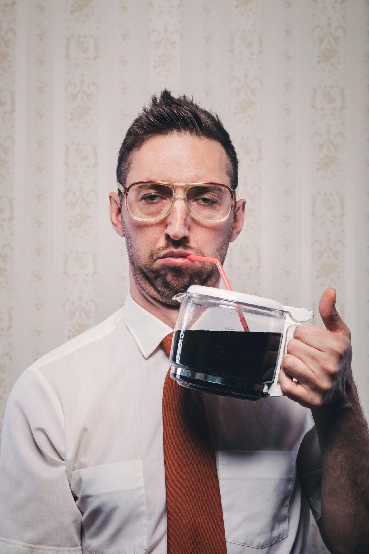Mann drikker kaffe med sugerør
