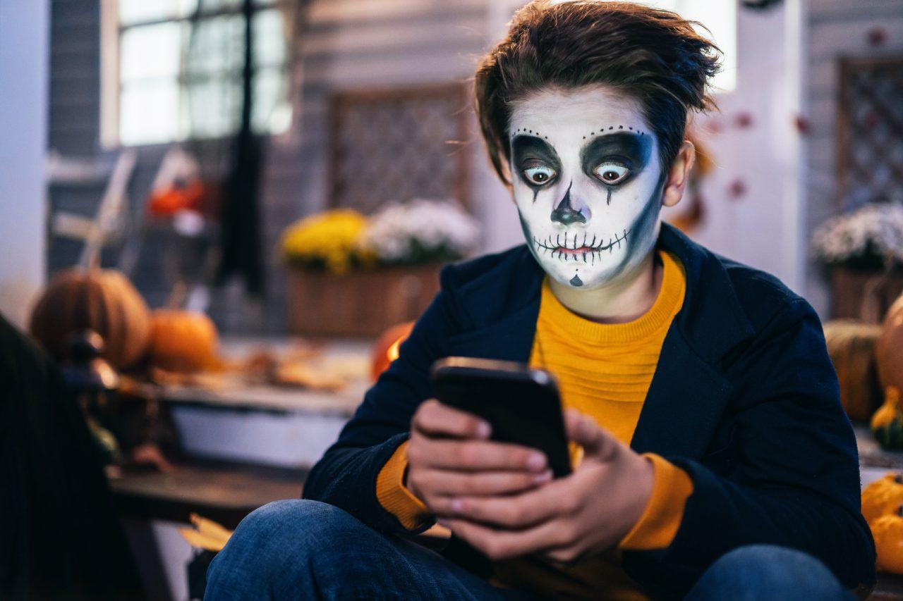 Halloween-gutt med mobiltelefon